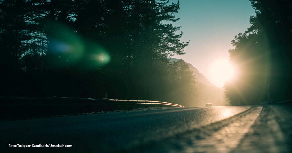 Bil som kjører inn i solnedgangen. Vei omgitt av trær.